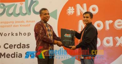 General Manager Sales Regional Sulawesi Telkomsel, Thomas A. Siaga, saat memberikan cendramata kepada salah satu perwakilan kepala sekolah.